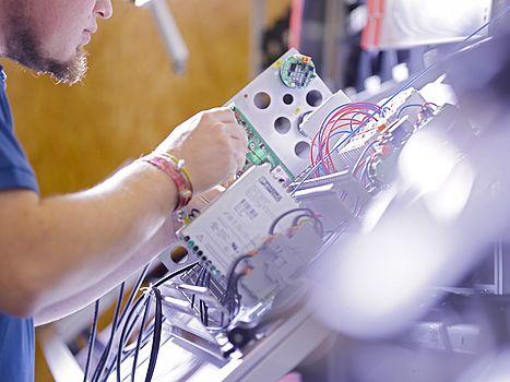 Techniker von AWITE Bioenergie schraubt an einem Bauteil